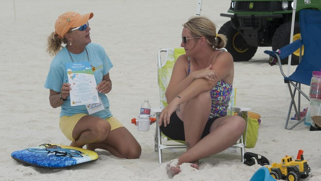 Beach Ambassador Monie Russo, left, politely reminds visitor Shannon Webb of some beach rules about picking up belongings before leaving the beach at the end day. The SRIA has re-launched it Beach Ambassador program once again, after a successful start last year.