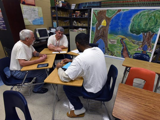 Inmates attending a substance abuse treatment program gather around a painting done by local artist Dawn Robinette, who donated the painting to the Read to Me, Daddy program at Bossier Correction Facility.