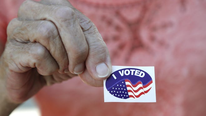 A Florida voter shows her sticker after she voted in the presidential primary, on March 17.