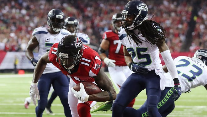 Atlanta wide receiver Julio Jones scores a touchdown past Seahawks cornerback Richard Sherman during the first quarter Saturday in an NFC divisional playoff game. The Falcons won, 36-20.