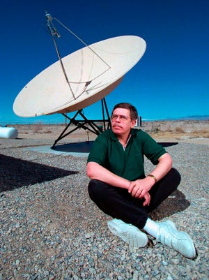 In this March 7, 1997 photo, late night talk show host Art Bell near a satellite dish at his Pahrump, Nev., home.