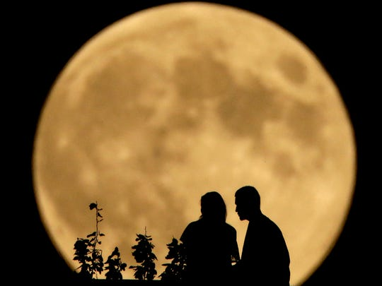 A couple sit on a bluff overlooking the Missouri River as the full harvest moon rises in the distance Sept. 8, 2014, in Kansas City, Mo.