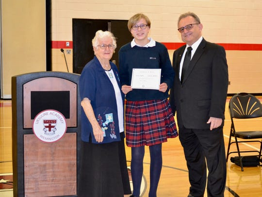 Ursuline student Grace Smith receives award for best essay addressing environmental issues from Maryknoll representatives Sister Mary and Brother John.