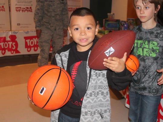 In this 2015 file photo, Desmond Macias holds two gifts he picked out, a basketball and a football, at the Otero County Toys for Tots Christmas event for children at the Sgt. Willie Estrada Memorial Civic Center on Christmas Eve 2015. This year the event is Dec. 23.