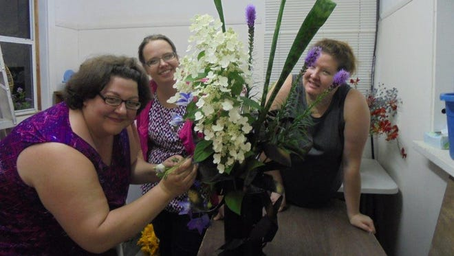 In the freshly painted flower show building, three fairly new competitors work to prepare their entries for the firstflower show for the Crawford County Fair. As Amy Vaughn (left) finishes with her creative mass, Julie Rexroad (behind) and Sarah Laipply (peeking through the liatris)seem to celebrate along with her. They are a strong team though new to floral arranging.