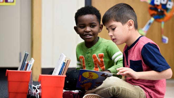 English-language learners Philmon Kalifa (left) and Edgar Tapia (right) read a book together in a combined first-grade and kindergarten class at the Elementary Immersion Center in Sioux Falls on Monday, Nov. 13, 2017.