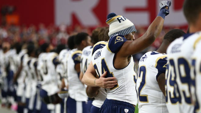 Rams linebacker Robert Quinn raises a fist during the national anthem prior to a game against the Cardinals on Dec. 2, 2017, at University of Phoenix Stadium.
