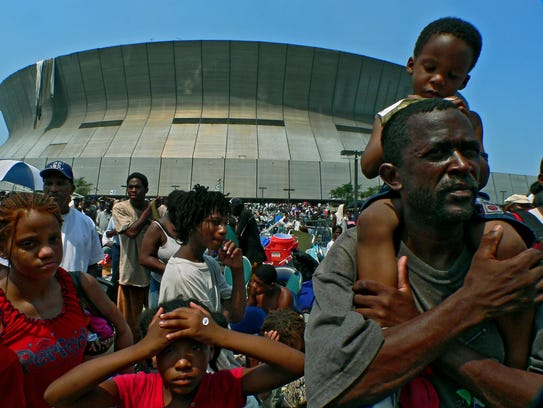 Hurricane Katrina victims wait for transportation outside