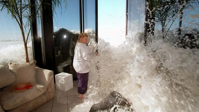 Too much, too fast: Marilyn Lane attempts to close her doors to prevent a large wave from crashing into the living room of her Solimar Beach home near Ventura, Calif.,  Jan. 30, 1998.  The 1997-98 El Nino brought a series of powerful storms to California.