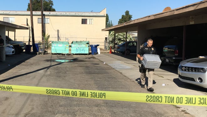 An officer with the Ventura Police Department carries a plastic bin from the scene of a fatal stabbing that occurred Aug. 13 in the 6300 block of Whippoorwill Street.