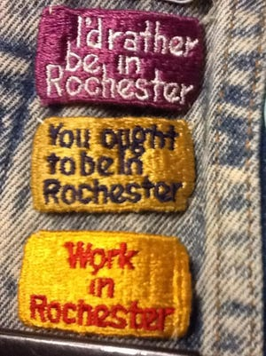 Badges with past mottoes promote Rochester pride.