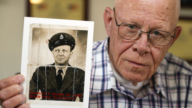 Retired veteran Paul Quinn holds a photograph of his father, Charles, who served in missions from World War II through the Cold War and the Cuban Missile crisis.