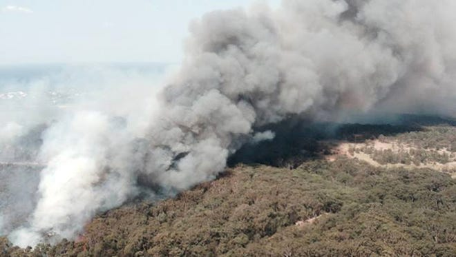 In this photo provided by the New South Wales Rural Fire Service, smoke rises from a wildfire near Lake Macquarie, New South Wales, Australia, on Oct. 23, 2013.
