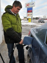 Nathan Brown, 39, of Wausau refuels his car Friday at the R-Store gas station on Grand Avenue in Wausau.