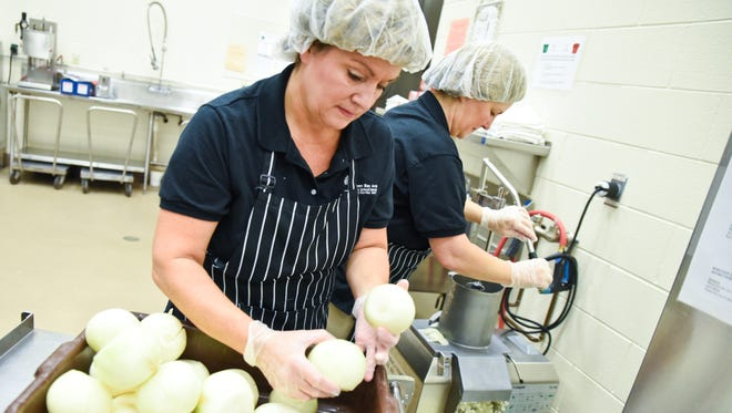 Co-workers Lisa Charneski and Brenda Nelson run onions through an industrial food processor during a special production day at the Green Bay School District's food service building on Friday.