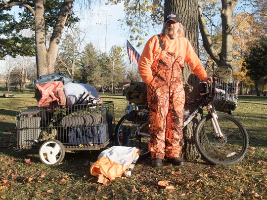 Vietnam Veteran Bob Finch stands with his bike that has many of his possessions. Finch, who has been homeless since 1997, says he likes it that way. He volunteers and handles the fire at the Night Without a Home event.