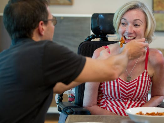 Jeff Berebitsky feeds pasta to his wife Jenni at their Indianapolis home. Suffering from ALS, Jenni needs help with things like feeding and mobility.