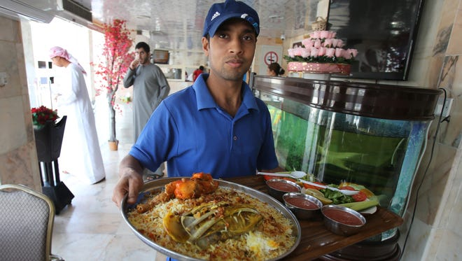 In this Tuesday, Dec. 23, 2014 photo, a waiter carries a tray of a mixed lamb and chicken Majboos, also known as Kabsa, at the Emirates Guest Cook restaurant in Shahama, about 90 kilometers southwest of Dubai, United Arab Emirates.