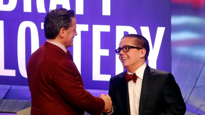 Cleveland Cavaliers owner Dan Gilbert congratulates his son Nick Gilbert after the team won the NBA basketball draft lottery, Tuesday, May 21, 2013 in New York.