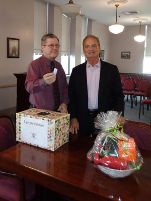 "Millville Board of Education president, Charles Flickinger (left), accepted three ""health-related"" gift baskets donated by Richard Allen of Allen Associates. Staff members who participated in an onsite flu clinic were invited to enter the drawing."