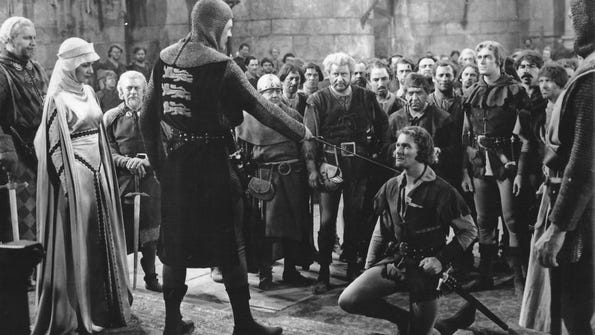 """Contributed photo Olivia de Havilland looks on as Errol Flynn is knighted in """"The Adventures of Robin Hood."""""""