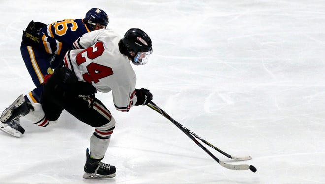Alec Elkin (24) of Neenah/Hortonville/Menasha takes a shot while being defended by Sam Sippel of Wausau West on Saturday at the Tri-County Ice Arena in Fox Crossing.