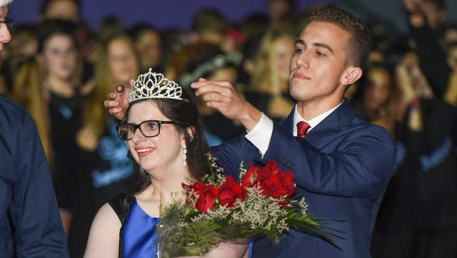 Riley McCoy has her crown placed by last year's homecoming king Jimmy Quick during halftime of the Dana Hills High School football game in Dana Point on Friday, September 15, 2017.