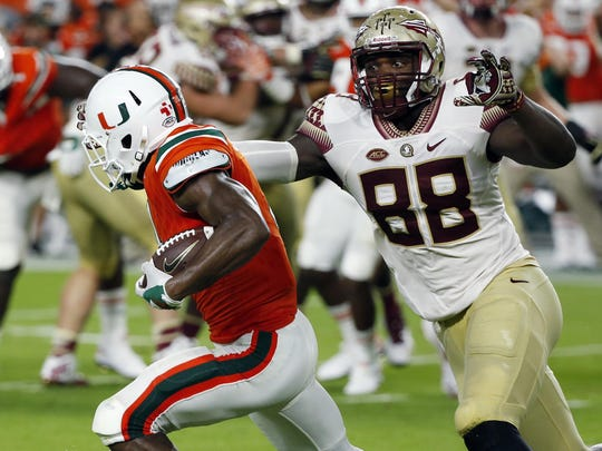 Miami defensive back Jaquan Johnson (4) intercepts a pass as Florida State tight end Mavin Saunders (88) attempts to tackle during the first half of an NCAA college football game, Saturday, Oct. 8, 2016, in Miami Gardens, Fla. (AP Photo/Wilfredo Lee)