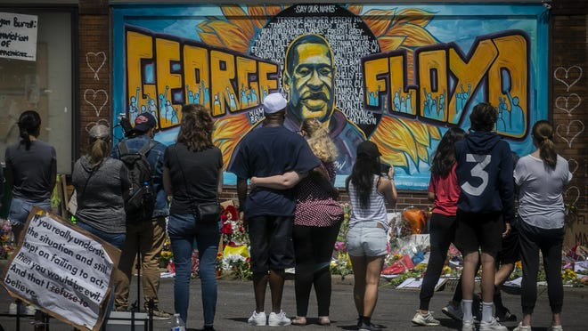 Visitors make silent visits to organic memorial featuring a mural of George Floyd, near the spot where he died while in police custody, Sunday May 31, 2020, in Minneapolis, Minn.