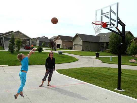 Emerson Manus, 8, plays basketball with her mother