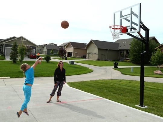 Emerson Manus, 8, plays basketball with her mother Danielle Seifert their home in the Prairie Trail subdivision in Ankeny on Thursday, June 18, 2015. The homes in the subdivision are built closer together but developers included ample public green space to make up for the lack of private yard space.