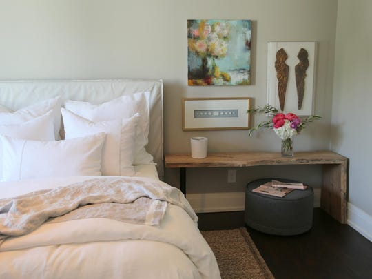In the upstairs bedrooms, Roxanne Jackson Interiors used low wooden benches for bedside tables and tucked an ottoman beneath.