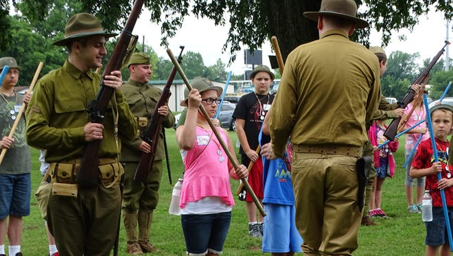 Junior members of the Ross County Historical Society get a lesson in how to be a World War I soldier from reenactors at the Camp Sherman Days event Saturday at the Ohio National Guard's Camp Sherman Joint Training Center.