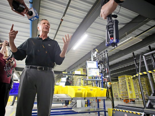 Ohio Governor John Kasich addresses the media Monday next to a work station at Amazon's Etna fulfillment center. The facility employs about 3,000 people who work alongside robots which can be seen working behind the fence.