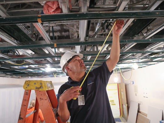 Cam Gomez with Tiller Constructors takes measurements in the interventional radiology laboratory of Desert Regional Medical Center, where the ceiling is being reinforced to withstand the motions of an earthquake, February 7, 2018.