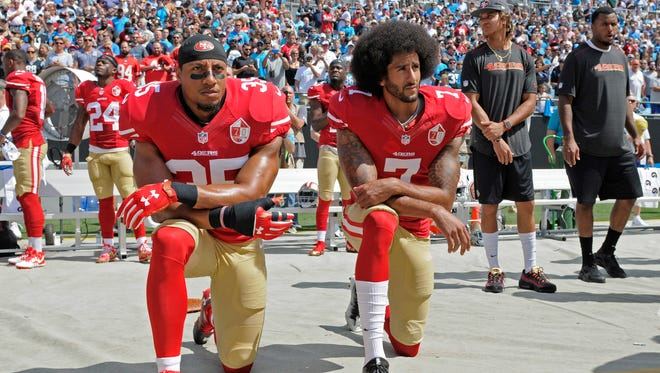 San Francisco 49ers' Colin Kaepernick (7) and Eric Reid (35) kneel during the national anthem before an NFL football game against the Carolina Panthers in Charlotte, N.C., Sunday.