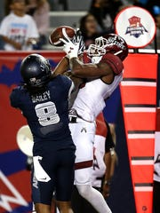 New Mexico State Aggies wide receiver Jaleel Scott (16) hauls in a fourth-quarter touchdown over Utah State Aggies cornerback Wesley Bailey (8) in the Utah State University and New Mexico State University in the NOVA Home Loans Arizona Bowl on Dec. 29, 2017, at Arizona Stadium in Tucson, Ariz. New Mexico State won 26-20 in overtime.