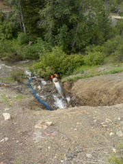 After erosion caused part of Highway 200 to fall, crews installed a temporary culvert to pump water from the north side of the highway to the south.