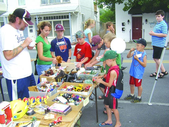 Kids and parents look over a table of various toys