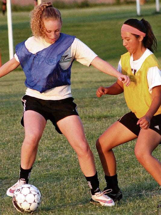 Kristen Guin, left, attempts to get past a defender at practice Thursday evening at the Riner Steinoff Soccerplex.