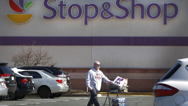 A shopper leaves the Pembroke Stop & Shop supermarket with supplies on Sunday March 15, 2020.
