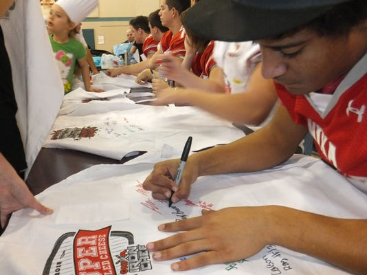 Nixa Iron Chef 5 Andrew Rivera along with the other football players sign ap.JPG
