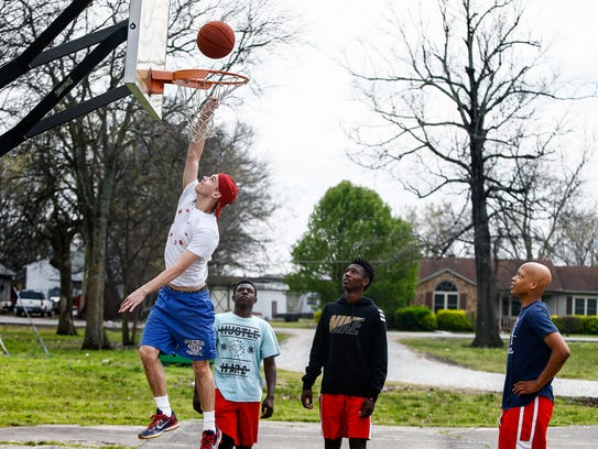 "Local kids play basketball at ""The Woodz,""  the courts"