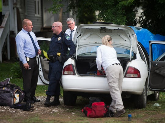 Members of the Knoxville Police Department raid a home on Huron Street in North Knoxville and search for evidence in a fatal shooting Tuesday May 23, 2017.