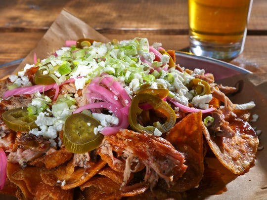 The pork nachos with kettle chips, smoked pork, pickled onion, jalape–o, feta with scallions and bbq sauce from Against The Grain. $10.50.