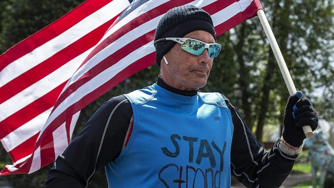 """John Scully, of Moorestown, NJ, shows his patriotic spirit against the coronavirus pandemic, as he runs up Main Street, in Moorestown carrying the American flag, as he wears a shirt saying """"Stay Strong,"""" on the front, and """"We Got This"""" on the back on Friday.  He has been running with the flag since the pandemic started and will continue till it ends."""