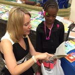 Jennifer Steenbock, literacy coach at Tank Elementary School in Green Bay, assists a student in selecting books.