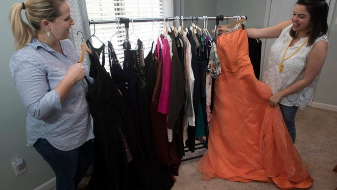 Pensacola FemFest organizers Sophia Young-Kiser, left, and Kristin Norris shows off some the clothing the group has collected as of Thursday, May 3, 2018. Pensacola Femfest is planning its first formal prom on  June 9.