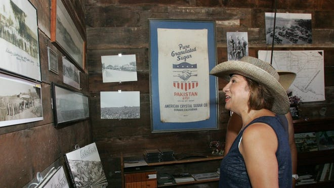 DAVID YAMAMOTO/SPECIAL TO THE STAR Imelda Ramirez looks at vintage photos on the wall of a barn where items are displayed during a barbecue Saturday at the Oxnard Historic Farm Park.