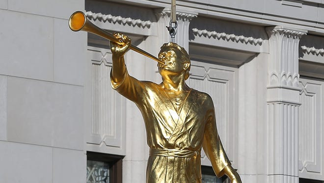 A statue of the ancient American Prophet Moroni is lifted atop the Indianapolis Mormon Temple in Carmel  on Friday, October 17, 2014. The gold-plated statue is 8.5 feet tall and weighs 900 pounds. It stands 106-feet above the ground.